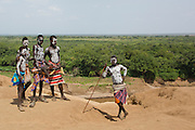 A group of young Karo tribe boys with AK-47 rifle . Omo Valley, Ethiopia