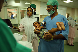 Doctors try to comfort a young boy while taking him into surgery at the Children's Hospital at the Pakistan Institute of Medical Sciences in Islamabad, Pakistan, Sept. 18, 2007.