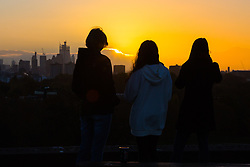 Friends enjoy the moment the sun appears from behind distant clouds as day breaks over London's skyline, seen from Primrose Hill, to the north of the city. London, November 13 2018.