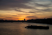 Golden sky at sunset looking over the River Thames at Wapping in East London, England, United Kingdom.