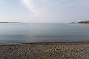 View out towards the horizon and sea on 15th September 2020 in Cemlyn, Anglesey, Wales, United Kingdom. Cemlyn is a bay on the northwest coast of Anglesey, North Wales, within the community of Cylch-y-Garn. Separated from the bay by a shingle beach is a brackish lagoon, which is fed by a number of small streams.