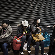 """Filipino women sit and chat in the street in Central on a Sunday, their weekly day off.  Hong Kong has a huge population of Filipinos, mostly woman who work as domestic workers in the business community. Most of the women have no private accomodation so on their days off Central Hong Kong is heaving with women who meet in puclic to socialize. <br /> <br /> <br /> Hong Kong (香港; """"Fragrant Harbour""""), officially known as Hong Kong Special Administrative Region of the People's Republic of China since the hand-over from the United Kingdom in 1997 under the principle of """"one country, two systsems"""".  7 million people live on 1,104km square, making it the most vertivcal city in the world. Hong Kong is one of the world's leading financial centres along side London and New York, it has one of the highest income per capita in the world as well the moste severe income inequality amongst advanced economies. The Hong Kong civil society is highly regulated but has at the same time one of the most lassiez-faire economies with low taxation and free trade. Civil unrest and political dissent is unusual but in 2014 the Umbrella Movenment took to the streets of Hong Kong demanding democracy and universal suffrage. 93 % are ethnic Chinese, mostly Cantonese speaking."""