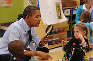 Decatur, Georgia - February 14, 2013:  United States President Barack Obama looks through a spy glass as a little girl stares at him inside a classroom at College Heights Early Childhood Learning Center on Thursday, February 14, 2013.  The five year-old girl didn't know who he was. He visited the school to highlight their pre-kindergarten. He is proposing a nationwide initiative to get more children into pre-kindergarten.  ©2013 Johnny Crawford