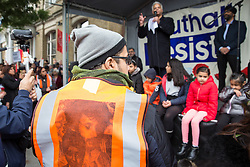 Southall, UK. 27th April 2019. A steward wearing a vest bearing the images of Gurdip Singh Chaggar and Blair Peach listens to Suresh Grover of Southall Resists at a rally outside Southall Town Hall to honour the memories of Gurdip Singh Chaggar and Blair Peach on the 40th anniversary of their deaths. Gurdip Singh Chaggar, a young Asian boy, was the victim of a racially motivated attack whilst Blair Peach, a teacher, was killed by the Metropolitan Police's Special Patrol Group during a peaceful march against a National Front demonstration.