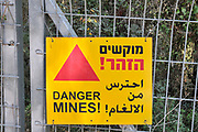"Israel,  A mine field, a yellow warning sign in Hebrew Arabic and English ""Danger Mines!"""