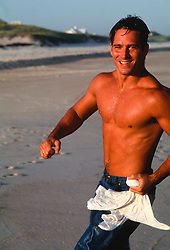 Shirtless wet man smiling and running on the beach