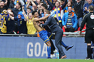 Lyle Taylor of AFC Wimbledon leaps onto Neal Ardley, the AFC Wimbledon manager as he celebrates after scoring his sides 1st goal to make it 1-0. Skybet football league two play off final match, AFC Wimbledon v Plymouth Argyle at Wembley Stadium in London on Monday 30th May 2016.<br /> pic by John Patrick Fletcher, Andrew Orchard sports photography.