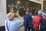 tourist taking a picture of a old painting Amsterdam Historical Museum