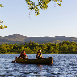 Two women paddle a canoe in the morning on Silver Lake in Piscataquis County, Maine. Near Greenville.