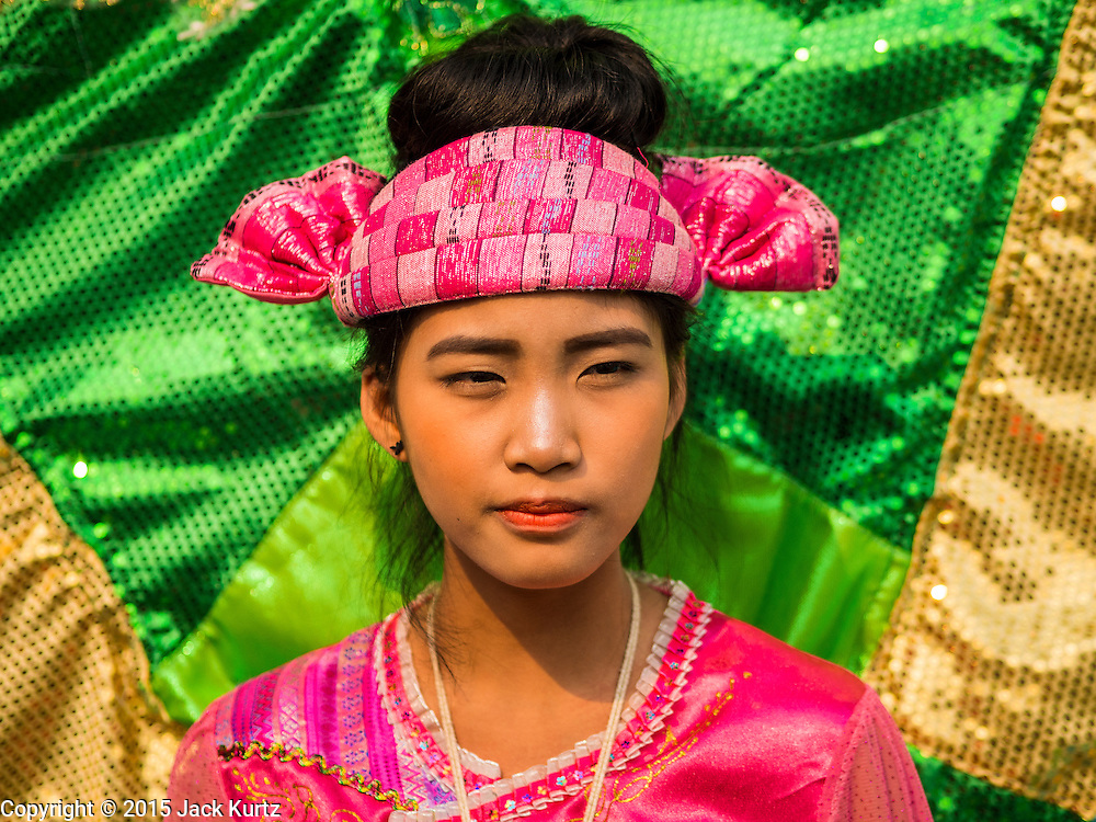 """05 APRIL 2015 - CHIANG MAI, CHIANG MAI, THAILAND: A Tai Yai woman dressed as a pea fowl, the national symbol of Myanmar (Burma) during the second day of the three day long Poi Song Long Festival in Chiang Mai. The Poi Sang Long Festival (also called Poy Sang Long) is an ordination ceremony for Tai (also and commonly called Shan, though they prefer Tai) boys in the Shan State of Myanmar (Burma) and in Shan communities in western Thailand. Most Tai boys go into the monastery as novice monks at some point between the ages of seven and fourteen. This year seven boys were ordained at the Poi Sang Long ceremony at Wat Pa Pao in Chiang Mai. Poy Song Long is Tai (Shan) for """"Festival of the Jewel (or Crystal) Sons.    PHOTO BY JACK KURTZ"""