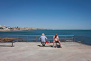 Men looking deep in thought on the seafront at Cascais, near Lisbon, Portugal.