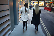 Two women whose clothes are the opposite of each other. Blonde hair and dark hair, white coat and black coat. City of London, UK.