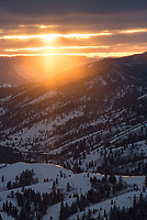 I stood on top of a peak in the Big Hole Mountains of Idaho after snowshoeing up. At first I was disappointed by all the clouds hiding the Tetons from view and making the light flat (the forecast called for sunny and clear). But then the clouds began to break up in the west and golden sunbeams (also known as crepuscular rays) danced across the ridges.