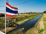 01 MARCH 2016 - CHACHOENGSAO, THAILAND: The Thai flag flutters over a nearly empty irrigation canal in Chachoengsao province of Thailand. Thai government officials have warned that there may not be enough water in the country's reservoirs to provide adequate water for farming, including fish and shrimp farms, industrial needs and domestic consumption. The government has told rice and fish farmers to reduce their use of water, and if necessary to reduce their crops. The current El Niño weather pattern is being blamed for the drought. The 2015 rainy season was well below normal and the 2016 rainy season could start two months late.    PHOTO BY JACK KURTZ