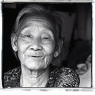 Black and white portrait of an old Vietnamese woman living along the railway of Hanoi, Vietnam, Southeast Asia