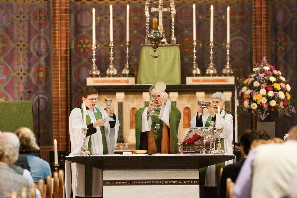 Annemieke Duurkoop (rechts) en Bernd Wallet (links) assisteren met de commune. Op zondag 31 oktober is in de Getrudiskathedraal in Utrecht  Annemieke Duurkoop als eerste vrouwelijke plebaan van Nederland geïnstalleerd. Duurkoop wordt de nieuwe pastoor van de Utrechtse parochie van de Oud-Katholieke Kerk (OKK), deze kerk heeft geen band met het Vaticaan. Een plebaan is een pastoor van een kathedrale kerk, die eindverantwoordelijk is voor een parochie. Eerder waren bij de OKK al twee vrouwelijk priesters geïnstalleerd, maar die zijn geen plebaan.<br /> <br /> Pastor Bernd Wallet (left) and dean Annemieke Duurkoop (right) are assisting the archbishop Joris Vercammen with the sacrament. At the St Getrudiscathedral in Utrecht the first female dean of the Old-Catholic Church (OKK), Annemieke Duurkoop, is installed together with a new pastor Bernd Wallet. The church has no connections with the Vatican.