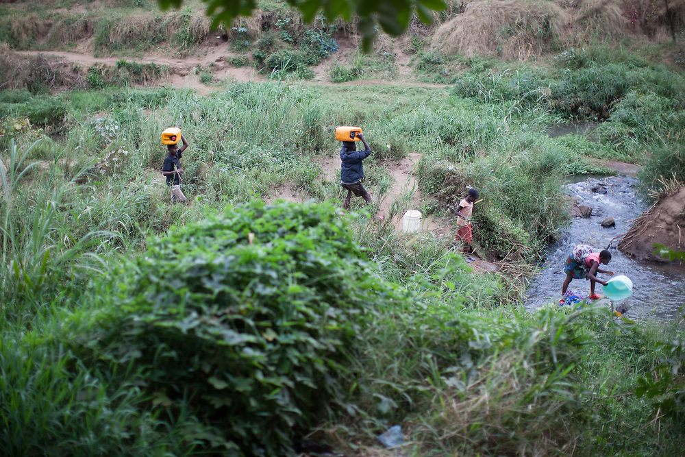 Boys carry jerry cans they've filled with water in a stream in southern Malawi. Girls are filling their recipients too. This is a daily necessity for families in the area as there are very few houses connected to a water supply.