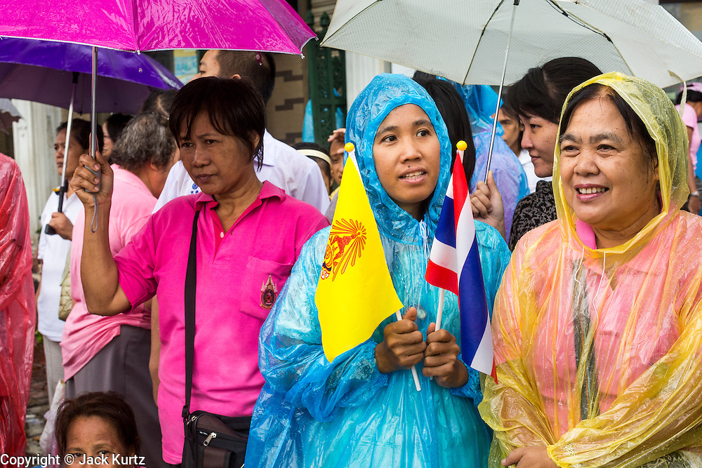 05 MAY 2013 - BANGKOK, THAILAND: Thais wait in the rain to see Bhumibol Adulyadej, the King of Thailand, Sunday. The King and Queen, who are both hospitalized and in poor health, did not attend Sunday's event. May 5 marks the 63rd anniversary of the Coronation of His Majesty King Bhumibol Adulyadej. The day is celebrated as a national holiday; since this year it falls on a Sunday, the holiday will be observed on Monday May 6, and as such all government offices and commercial banks will close for the day. HM King Bhumibol Adulyadej is the longest reigning monarch in the world. Each year on the 5th of May, the Kingdom of Thailand commemorates the day when, in 1950, the Coronation Ceremony was held for His Majesty King Bhumibol Adulyadej, the 9th in the Chakri Dynasty (Rama IX). On the 5th of May, His Majesty conducts a merit making ceremony, presenting offerings to Buddhist monks, and leads a ?Wien Thien? ceremony, walking three times around sacred grounds at the Temple of the Emerald Buddha. PHOTO BY JACK KURTZ