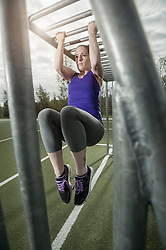 Young woman doing chin-ups on football ground, Bavaria, Germany