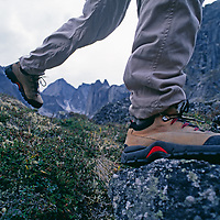 A hiker walks through tundra in the Cirque of the Unclimbables.