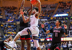Dec 14, 2019; Morgantown, WV, USA; West Virginia Mountaineers guard Miles McBride (4) drives down the lane while defended by Nicholls State Colonels guard Andre Jones (13) and Nicholls State Colonels guard Jeremiah Buford (11) during the second half at WVU Coliseum. Mandatory Credit: Ben Queen-USA TODAY Sports