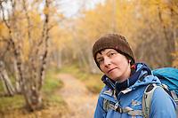 Portrait of female hiker in yellow Autumn birch forest along Kungsleden trail, near Abisko, Lappland, Sweden