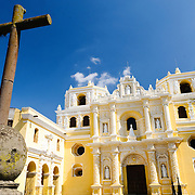 The bright yellow Church and Convent of Our Lady of Mercy (Iglesia y Convento de Nuestra Senora de la Merced) in Antigua, Guatemala, with iron cross at left of frame and yellow church in the background.