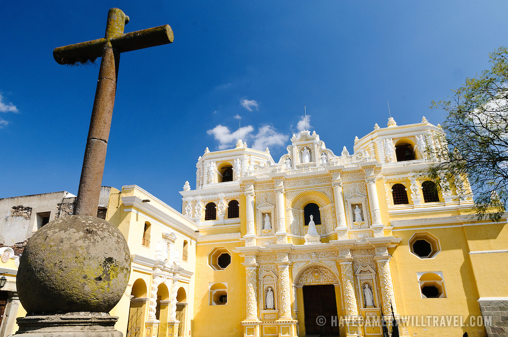 The bright yellow Church and Convent of Our Lady of Mercy (Iglesia y Convento de Nuestra Senora de la Merced) in Antigua, Guatemala, with iron cross at left of frame and yellow church in the background.