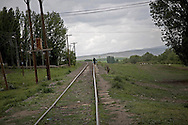 Akyaka resident on his way home from town walking along railway trucks...Akyaka is a last town and train stop on the way to Armenian border-and Gyumri  in Armenia .Border is about 10 km further on..