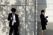 businesspeople one making a call and the other a text message with their cellphones