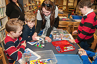 "Angela Stafford demonstrates to Lucca Santos and Mason Sleeper how to attach their flip book card during Elm Street School's ""Let Go Your Mind"" Lego program after school on Tuesday.  (Karen Bobotas/for the Laconia Daily Sun)"
