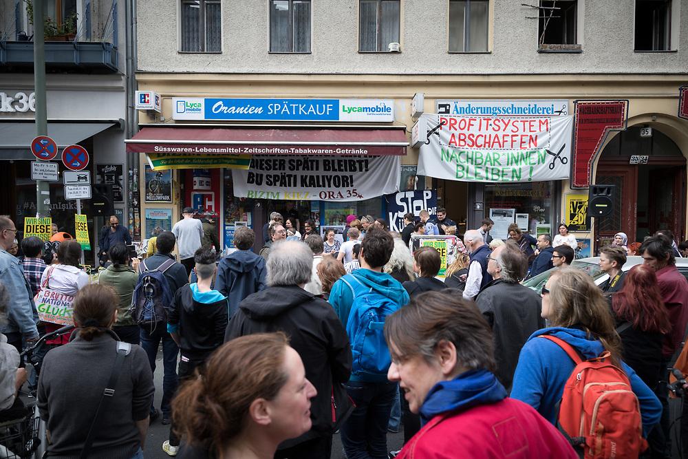 An die 100 Anwohner und Nachbarn protestieren vor der Oranienstrasse 35 in Berlin Kreuzberg gegen die Verdraengung eines Spätis und einer Änderungsschneiderei. Der Spätkauf von Zekiye Tunc hat eine Raeumungsklage gegen einen ehemaligen Eigentuemer des Hauses verloren, der neue Investor Bauwerk Immobilien GmbH hat Anfragen zu einer Verlaengerung des Mietvertrages ignoriert. Der Aenderungsschneiderei von Binnaz Kabacaoglu wurde nach Protesten eine Verlaengerung des Mietvertrages auf zwei Jahre angeboten, ohne dabei konrete Angaben über die neue Miethöhe zu machen. <br /> <br /> [© Christian Mang - Veroeffentlichung nur gg. Honorar (zzgl. MwSt.), Urhebervermerk und Beleg. Nur für redaktionelle Nutzung - Publication only with licence fee payment, copyright notice and voucher copy. For editorial use only - No model release. No property release. Kontakt: mail@christianmang.com.]