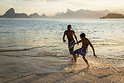 Boys playing football on Niteroi beach with a view of the Guanabara bay, Christ the Reedemer statue and the Sugar Loaf mountain, Rio de Janeiro.