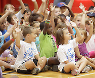 Middletown, New York - Children from the Middletown YMCA summer camp raise their hands during a Mad Science demonstration on August 20, 2010.