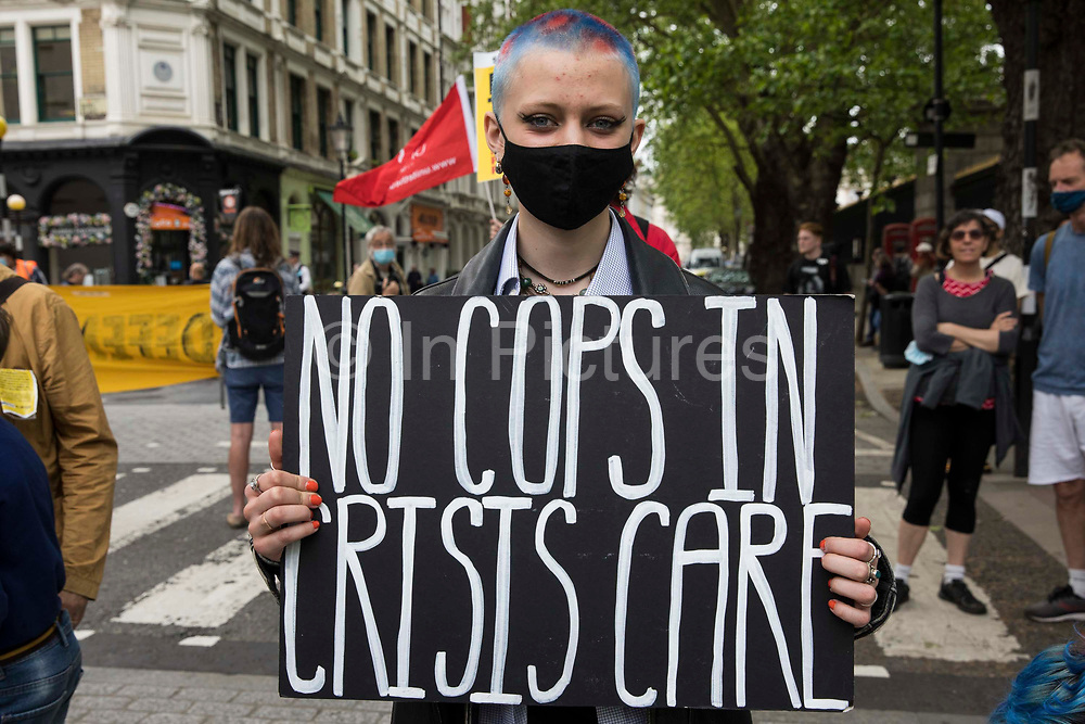 An activist holds a sign reading No Cops In Crisis Care during a Kill The Bill National Day of Action in protest against the Police, Crime, Sentencing and Courts PCSC Bill 2021 on 29th May 2021 in London, United Kingdom. The PCSC Bill would grant the police a range of new discretionary powers to shut down protests, including the ability to impose conditions on any protest deemed to be disruptive to the local community, wider stop and search powers and sentences of up to 10 years in prison for damaging memorials.