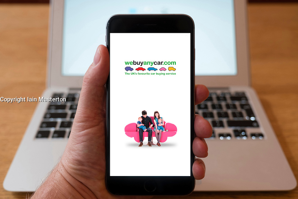 Using iPhone smartphone to display homepage form Webuyanycar.com e-commerce website