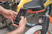 Using a mobile telephone application to get the code to unlock a shared bike<br /><br />Bike sharing in China has multiplied over the years with various brands offering shared bikes which can be unlocked using an application on your mobile telephone, and then locked and left anywhere for the next rider. Ofo and Mobike are the two world leaders. One of the problems is the huge over supply of bikes, which has meant many startups going out of business, and huge bike cemeteries created on the outskirts of China's mega cities, where hundred's of thousands of bikes are rusting away.