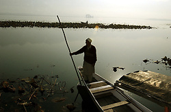 A Kashmiri man prepares to take his canoe across Srinagar's Dal Lake in the troubled state of Kashmir Sunday, November 18, 2001.  Kashmir's beauty is unmatched and once had a thriving tourism industry but because of the war, it has come to a virtual and complete halt.  The war in Kashmir has been going on since 1989 when militant organizations chose to fight for secession from India and now the war in Afghanistan  has made the region even more volatile . (Photo by Ami Vitale/Getty Images)