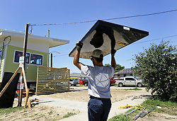 26 August 2015. New Orleans, Louisiana. <br /> Hurricane Katrina revisited. <br /> Rebuilding the Lower 9th Ward. <br /> Emil Christmann, a contractor with Joule Solar Energy works on a new 'Make it Right' house. Eco friendly 'Make it Right' houses inspired by actor Brad Pitt continue to provide hope for the rebirth of the community following the devastation of hurricane Katrina a decade earlier.<br /> Photo credit©; Charlie Varley/varleypix.com.