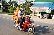Man and a Buddhist monk travel on a motorcycle, Bangkok, Thailand