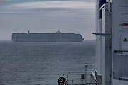 Container ships out at sea in the English Channel on 26th September 2021 between France and the United Kingdom. This large OOCL vessel is stacked high with containers from different companies. This is still the major way that goods are transported around the World.