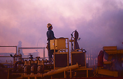 Stock photo of an oilfield worker manning pumps during secondary recovery operations in East Texas.