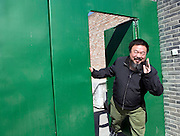 Chinese artist Ai Weiwei waves at the gate of his studio in northern Beijing. Ai is is one of the leading artists as well as independent curators and architectural designers in China.