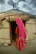 Islam-u-din's sister enters her yurt. The red flowing veil is called Jorluk. At Effendi Boi's summer camp of Aq Jilga.<br /> <br /> Adventure through the Afghan Pamir mountains, among the Afghan Kyrgyz and into Pakistan's Karakoram mountains. July/August 2005. Afghanistan / Pakistan.