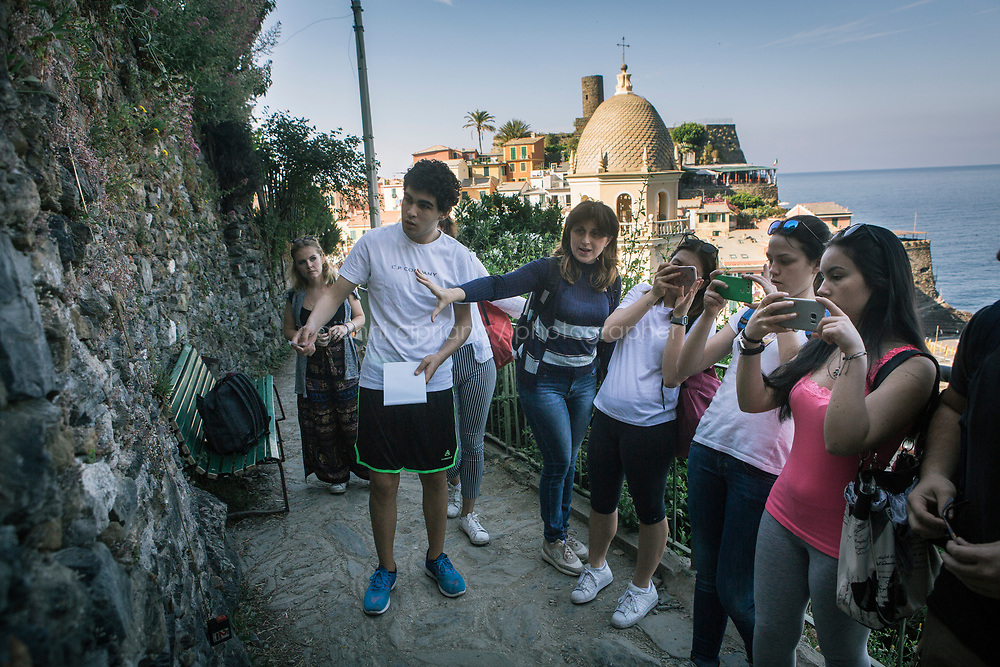 VERNAZZA, ITALY - 1 JUNE 2017: A high-school class takes measures during a field trip with Margherita Ermirio, part of a UNESCO Youth program to enhance the relationship between the young and their territory, here in Vernazza, Italy, on June 1st 2017. This class has been studying terracing in the Cinque Terre from an historical point of view, comparing the 18th century maps with Google earth's most recent pictures. From the measures taken during the field trip, students will make a 3D design of the area.<br /> <br /> Given its jagged coastline and manifold mountainous chains, Italy is believed to hold a record in Europe with an estimated 300,000 hectares of terracing, and 170,000 kilometers of dry stone walls— 20 times the length of the Great Wall of China.<br /> Liguria, the narrow half-moon shaped region along the northern<br /> Thyrrenian sea, has the highest concentration, and terracing is in<br /> poor shape there. In Vernazza, almost half of the terracing is in<br /> ruins.<br /> <br /> Terraced vineyards, apple and lemon groves horizontally run around the green slopes of the Cinque Terre. The stone walls have allowed such vital cultivation in the area and prevented land slides. Since the 1960s, the ancient walls have been largely<br /> abandoned, posing hydro-geological threats to the same villages during<br /> heavy rains and, in general, as time passes.<br /> <br /> Since the 2012 flood - when tons of mud invaded the<br /> village's main road, shops and and homes, isolating the area and<br /> taking three lives - Margherita Ermirio has agreed with the various land lords to take<br /> over 6,000 square meters of land parcels that needed to be cleaned up,<br /> in order to fix them and thus prevent land slides, but also to show to<br /> the younger generations that agriculture is still possible in the<br /> Cinque Terre.