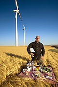 John Opris, a wind farm operations manager for enXco, with 265-foot wind turbines and his typical day's worth of food in Birds Landing, California. (From the book What I Eat: Around the World in 80 Diets.) The caloric value of his day's worth of food in July was 3700 kcals. He is 50 years of age; 5 feet, 10 inches tall; and 180 pounds. Each 265-foot  wind turbine produces enough electricity per year to power 350 average-size California homes.  MODEL RELEASED.