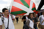 Waving the Basque flag, spectators from Bayonne in Basque France walk through the Olympic Park during the London 2012 Olympics. This land was transformed to become a 2.5 Sq Km sporting complex, once industrial businesses and now the venue of eight venues including the main arena, Aquatics Centre and Velodrome plus the athletes' Olympic Village. After the Olympics, the park is to be known as Queen Elizabeth Olympic Park.
