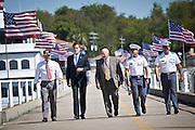 Republican presidential candidate Mitt Romney walks with USS Yorktown Director Mac Burdette (L) and Adm. Jim Flatley III (C) during a visit to the USS Yorktown museum on October 6, 2011 in Charleston, South Carolina. Romney addressed a group of veterans and called for increased military spending to maintain national security.