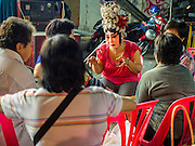 "18 AUGUST 2014 - BANGKOK, THAILAND:   A member of the Lehigh Leng Kaitoung Opera troupe chats with members of the audience during a performance at Chaomae Thapthim Shrine, a small Chinese shrine in a working class neighborhood of Bangkok. The performance was for Ghost Month. Chinese opera was once very popular in Thailand, where it is called ""Ngiew."" It is usually performed in the Teochew language. Millions of Chinese emigrated to Thailand (then Siam) in the 18th and 19th centuries and brought their culture with them. Recently the popularity of ngiew has faded as people turn to performances of opera on DVD or movies. There are still as many 30 Chinese opera troupes left in Bangkok and its environs. They are especially busy during Chinese New Year and Chinese holiday when they travel from Chinese temple to Chinese temple performing on stages they put up in streets near the temple, sometimes sleeping on hammocks they sling under their stage. Most of the Chinese operas from Bangkok travel to Malaysia for Ghost Month, leaving just a few to perform in Bangkok.      PHOTO BY JACK KURTZ"