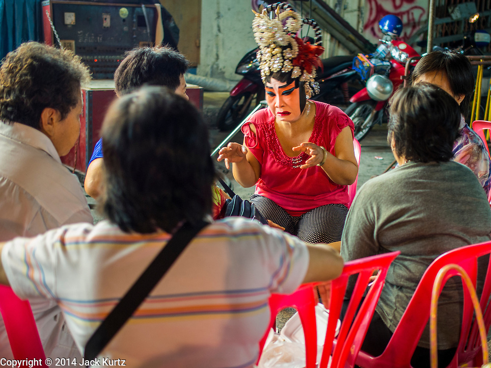 """18 AUGUST 2014 - BANGKOK, THAILAND:   A member of the Lehigh Leng Kaitoung Opera troupe chats with members of the audience during a performance at Chaomae Thapthim Shrine, a small Chinese shrine in a working class neighborhood of Bangkok. The performance was for Ghost Month. Chinese opera was once very popular in Thailand, where it is called """"Ngiew."""" It is usually performed in the Teochew language. Millions of Chinese emigrated to Thailand (then Siam) in the 18th and 19th centuries and brought their culture with them. Recently the popularity of ngiew has faded as people turn to performances of opera on DVD or movies. There are still as many 30 Chinese opera troupes left in Bangkok and its environs. They are especially busy during Chinese New Year and Chinese holiday when they travel from Chinese temple to Chinese temple performing on stages they put up in streets near the temple, sometimes sleeping on hammocks they sling under their stage. Most of the Chinese operas from Bangkok travel to Malaysia for Ghost Month, leaving just a few to perform in Bangkok.      PHOTO BY JACK KURTZ"""